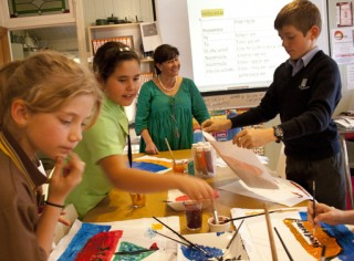 Children painting in class with Patricia